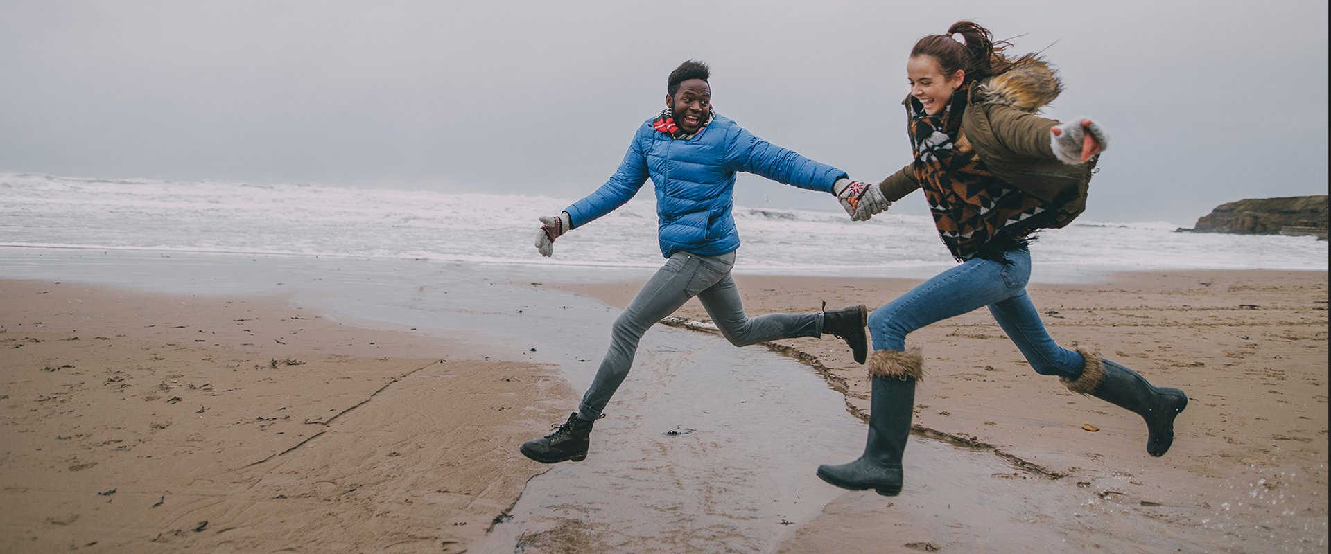Young Couple Leap Along A Winter Beach